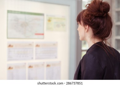 Young woman with her red hair in a bun standing reading notices on a bulletin board indoors, profile view from behind