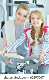 Young woman with her teenage daughter in a gym