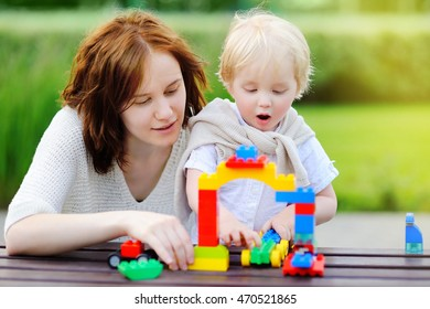 Young woman with her toddler son playing with colorful plastic blocks outdoors