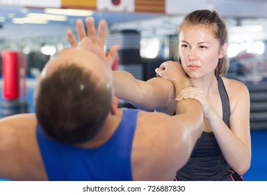 Young woman and her trainer are practicing punches on the self-defense course in gym