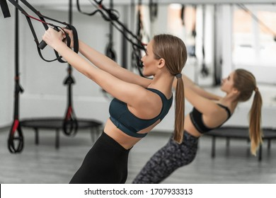 Young woman and her trainer training exercise push ups with trx fitness straps in the gym concept , sport workout and healthy lifestyle.