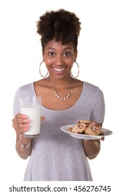 Young woman in her twenties holding a glass of milk and a plate of cookies