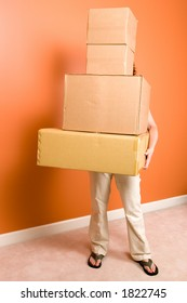 Young woman hidden behind the tall stack of boxes she is carrying. Concept is moving into a new home or college dorm.