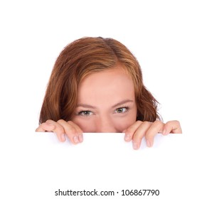 Young woman hiding behind a billboard and looking on camera isolated on white background