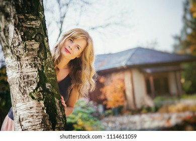 Young woman hiding behind the tree in autumn park