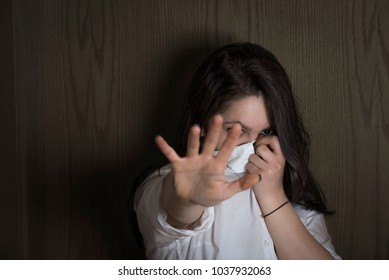 Young woman hiding her face with her shirt while stretching her hand toward the camera in order not to be seen, on a wooden background, in shadows.