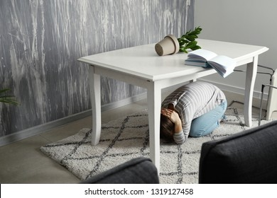 Young woman hiding under table during earthquake
