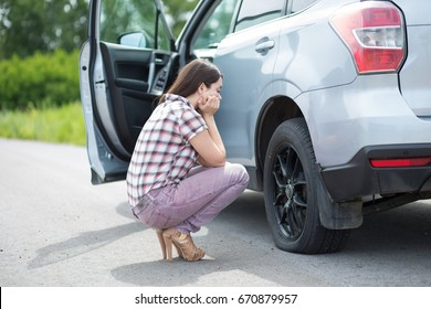Young woman with high heels in the city with flat tire, frustrated near broken car