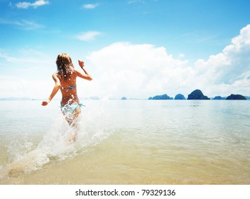 Young woman hight speed running into sea with splashes