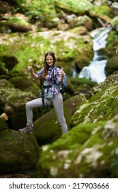 Young woman hiker with backpack crossing a river among boulders covered with moss in a canyon