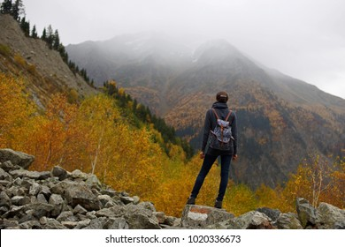 Young woman hiker with backpack standing on stones in front of high mountain in fog and colorful autumn forest, view from back, Svaneti, Georgia