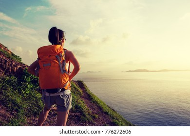 Young woman hiker with backpack standing at seaside mountain