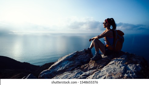 Young woman hiker enjoy the view at sunrise seaside mountain peak - Shutterstock ID 1548655376