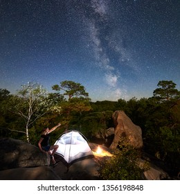 Young woman hiker having a rest on rocky mountain top beside camp, campfire and glowing tourist tent at summer night, pointing at sky full of stars and Milky way. On background boulders and trees