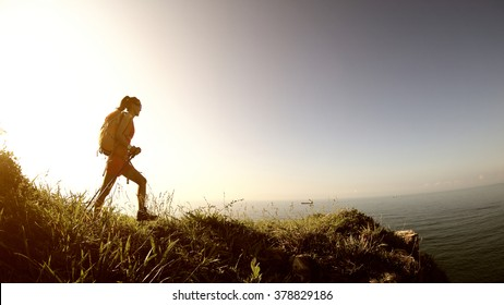 young woman hiker hiking on sunrise mountain peak