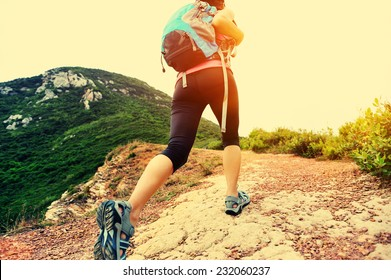 young woman hiker legs walking on seaside mountain trail