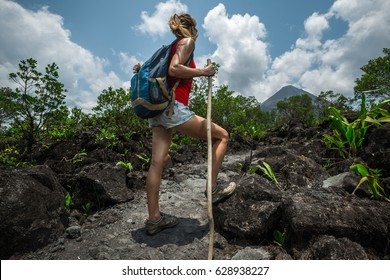 Young woman hiker relaxing on the trail and watching volcano on the horizon