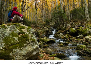 Young woman hiker resting on a big rock in the forest by a stream enjoying the peace and beauty of autumn.