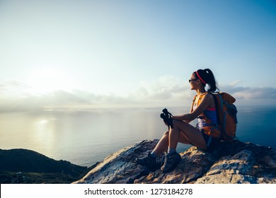 Young woman hiker sit at sunrise seaside mountain peak looking at the view - Shutterstock ID 1273184278