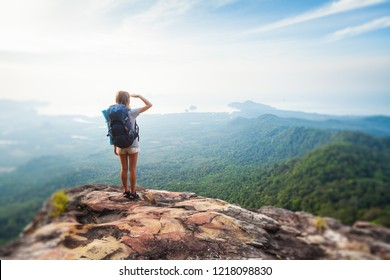 Young woman hiker stands with backpack on the cliff and looks into valley and sea coastline. Tilt shift effect applied