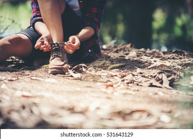Young woman hiker stops to tie her shoe on a summer hiking trail in forest.