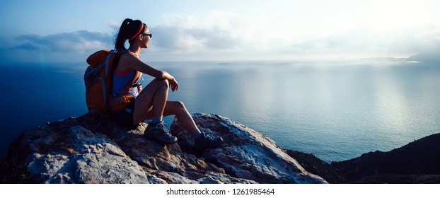 young woman hiker at sunrise seaside mountain peak
