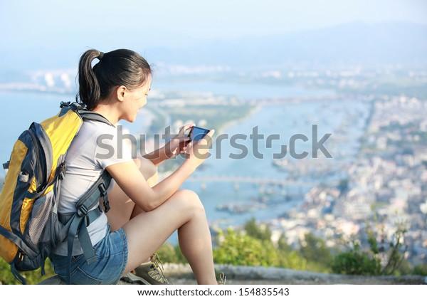 young woman hiker use smart phone mountain peak