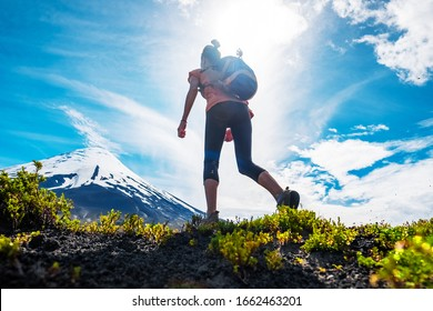 Young woman hiker walks on the trail with snow capped volcano of Osorno on the background, Chilean Patagonia
