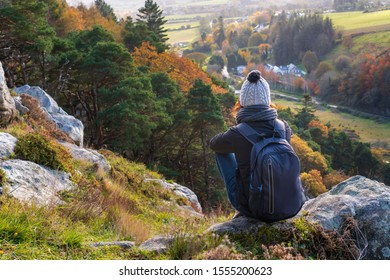 Young woman hiker wearing warm and cozy clothing, resting on a rock in Dublin Mountains, Ireland on a lovely fall day and enjoying the autumnal view from above. Irish autumn scenery.