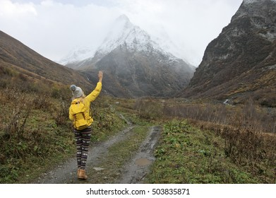 Young woman hiker in yellow clothing walking in valley to snowy mountains at rainy weather.