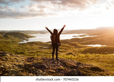 Young woman hikes in the mountain with beautiful view on the lake Ustevatnet near Geilo in Norway in the National park Hardangervidda at sunset with warm red light. Blurred background.