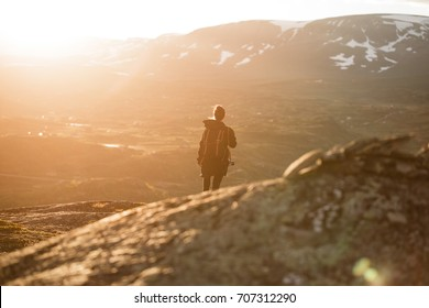 Young woman hikes in the mountain in Norway in the National park Hardangervidda at sunset with warm red light. Blurred background. Stoned blurred foreground.