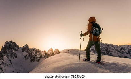 Young woman hiking alone in the snowy mountains during sunset