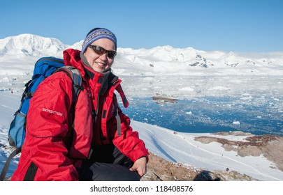 Young woman hiking with backpack in mountains, Antarctica