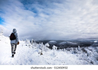 Young Woman Hiking High in the Mountains during Winter