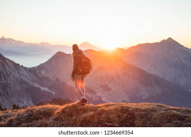 Young woman hiking into sunset in beautiful mountain landscape