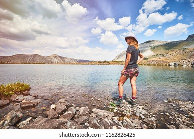 a young woman hiking next to a high alpine lake in the mountains of Colorado