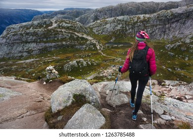 Young woman hiking in Norway, Kjerag trail. Summertime in the mountains. Active vacation.