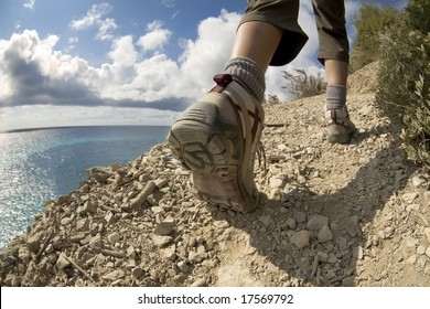young woman hiking on a cliff near the sea