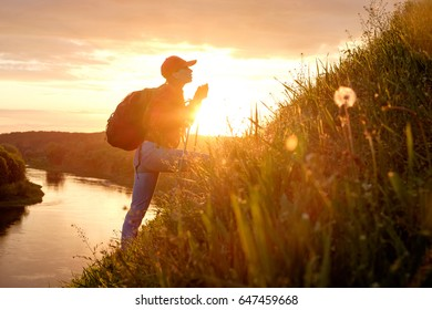 Young woman hiking over hills with backpack and hiking sticks