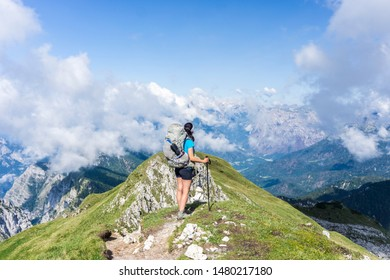 Young woman hiking in shorts with big backpack and trekking pole on the top of a mountain, sky full of clouds - Dolomites, Veneto, Italy