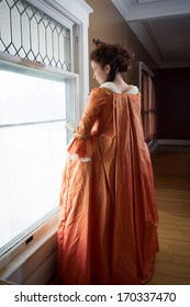 A young woman in historical clothing in the window of an 18th century mansion