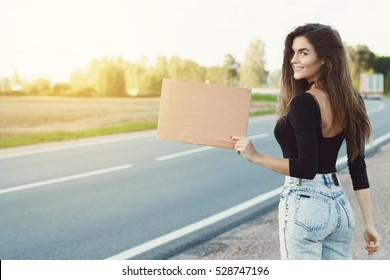 Young woman hitchhiker on the road is holding a blank cardboard sign