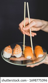 Young woman hold bowl in her hands full of  sushi with salmon and srimp. japanese food concept.