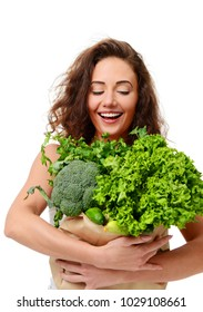 Young woman hold grocery paper shopping bag full of fresh green vegetables. Diet healthy eating concept.