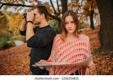 Young woman hold map and look at camer.a She is frustrated. Guy look in binoculars. They exploring.