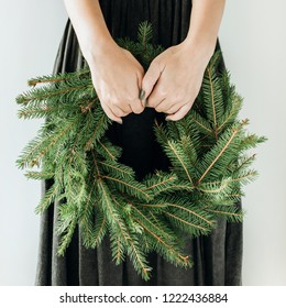 Young woman hold wreath frame made of fir branches. Christmas / New Year composition.