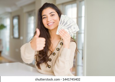 Young woman holding 20 dollars bank notes happy with big smile doing ok sign, thumb up with fingers, excellent sign