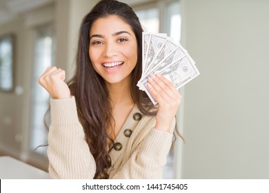 Young woman holding 50 dollars bank notes screaming proud and celebrating victory and success very excited, cheering emotion
