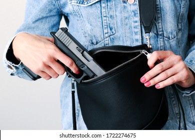 Young woman holding 9mm handgun in purses for concealed weapons.